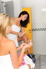 Locker room two sportive women applying lotion