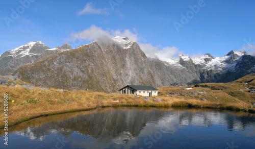 Mountains and hut lake reflection