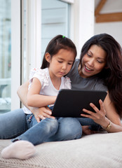 Happy Mother and Daughter with Digital Tablet