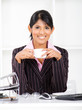 young indian businesswoman with coffee in office