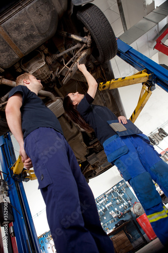 Two Mechanics Looking at Car