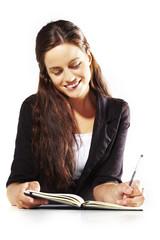 Mujer sonriendo escribiendo en agenda en fondo aislado