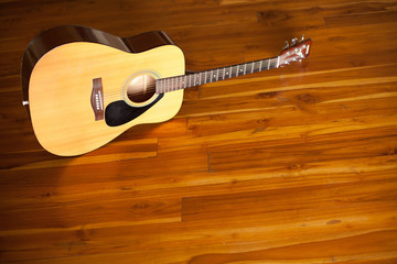 acoustic guitar on wooden floor