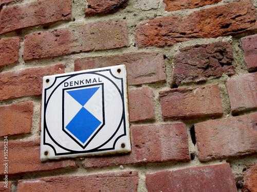 Leinwanddruck Bild Denkmal Schild an Backsteinmauer