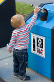 child putting waste in bin
