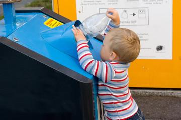 child putting waste in bin