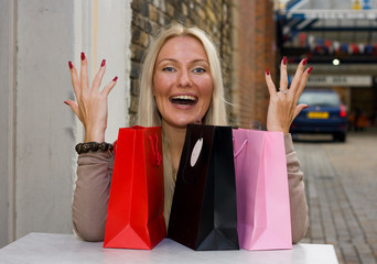 excited woman with shopping bags sitting outside a cafe.