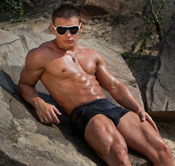 Muscle sexy wet naked young man lying on the rock