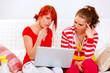 Bewildered girlfriends looking in laptops screen