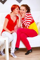 Girl whispering gossips in ear of her interested girlfriends