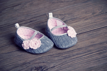 girl baby shoes placed on a wooden floor