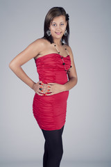 Young model in red dress posing fashion in studio