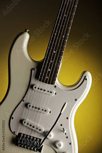 White Guitar Isolated On Yellow Spotlight