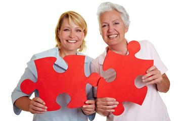 Frauen halten Puzzleteile
