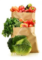Raw vegetables and shopping bag isolated on white
