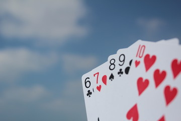 Poker hand - Straight Flush, with sky background