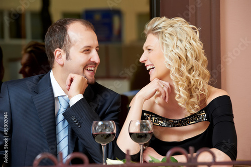 Man and girl with wine at cafe on a date