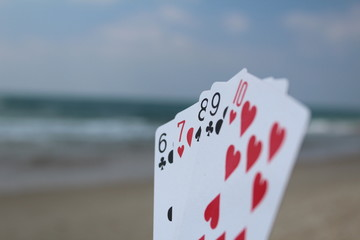 Poker hand - Straight Flush, with beach background