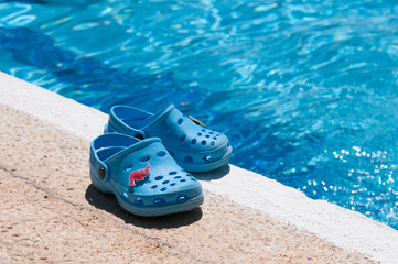 Chanclas azules al borde de piscina