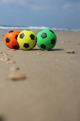 Three colorful balls at the beach