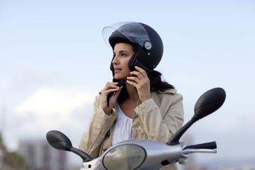 Attraktive Frau auf Roller zieht ihren Helm aus