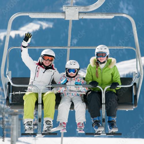 Ski lift - happy skiers on ski  vacation