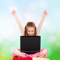 A young girl with a laptop sitting have joyfully hands up