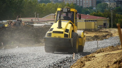 a road construction by a red road roller