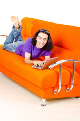 Student working with laptop sitting on sofa