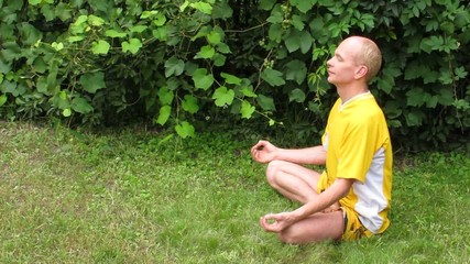 Man in yellow in meditation. On grass.