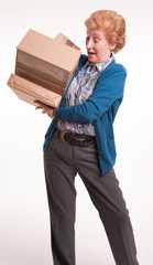 Busy senior woman with heavy parcels