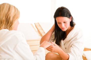 Beauty spa room two women showing manicure