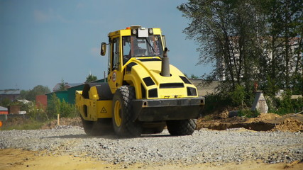 a road construction by a yellow road roller