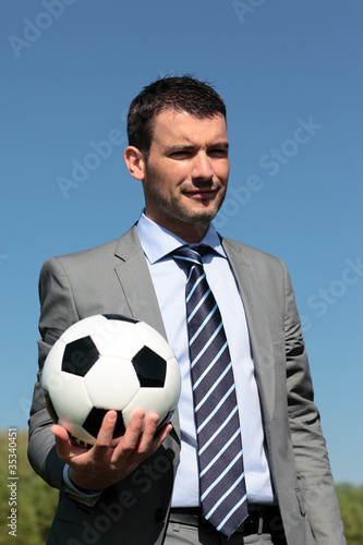 coach with ball in a park in summer