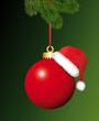 Rote Christbaumkugel mit Weihnachtsmütze und Tannenzweige