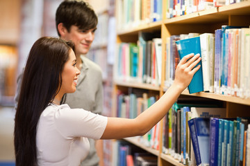 Students choosing a book on a shelf