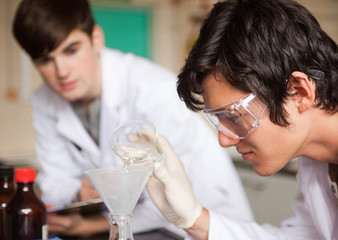 Close up of students in chemistry making an experiment