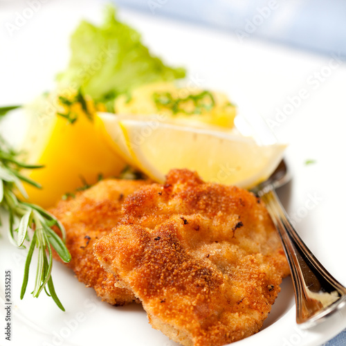 Schnitzel with potatoes, rosemary sprig and lemon