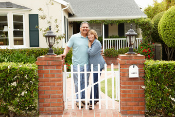 Senior Hispanic couple outside home