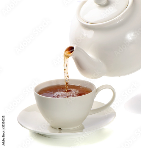 Tea being poured into tea cup isolated on a white background