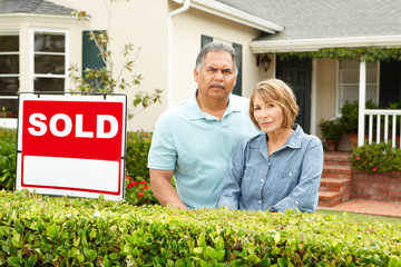 Senior Hispanic couple outside house with sold sign