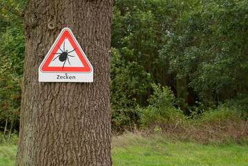 Warnschild Zecken an einem Baum am Waldrand