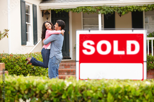 Hispanic couple outside home with sold sign - 35359686