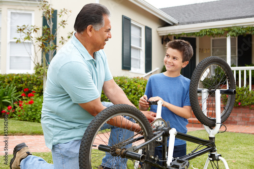 boy and grandfather fixing bike
