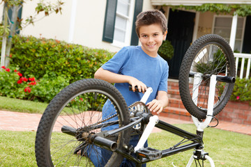 boy fixing bike in garden