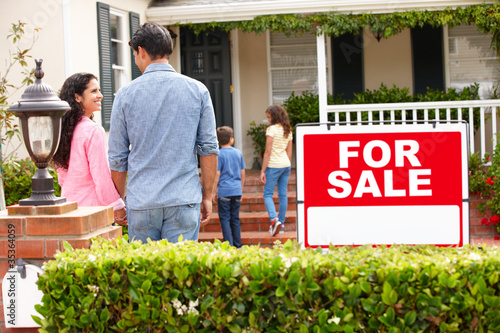 Hispanic family outside home with for sale sign