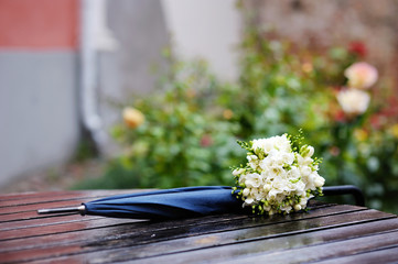 Rainy wedding: bridal flowers and umbrella on wet table