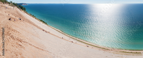 Foto op Plexiglas Grote meren Tourists climbing a popular dune at Sleeping Bear Dunes.