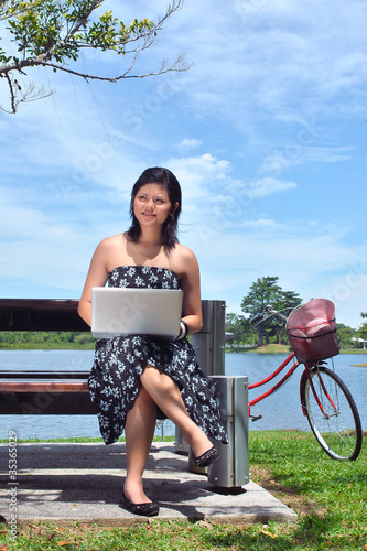 pretty girl with laptop and bicycle at  lake