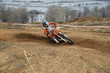 Motorbike racer turns sharply to the on a sandy track